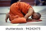 YANGON, MYANMAR - NOV 15: An unidentified buddhist monk kneels down in prayer on Nov 15, 2011 in Yangon, Myanmar. - stock photo