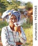 BAGAN, MYANMAR - NOV 17: An unidentified woman smokes a traditional cheroot cigar on Nov 17, 2011 in Bagan, Myanmar. - stock photo