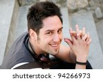Portrait of young smiling man sitting on steps, with headphones - stock photo