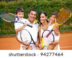 Happy family playing tennis holding rackets at the court - stock photo