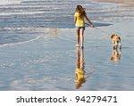 Girl Walking Dog On Beach