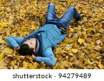 Young stylish man laying in foliage in autumn park. Outdoor. - stock photo