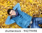 Young smiling man portrait laying in foliage in autumn park. Outdoor. - stock photo