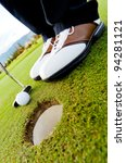 Golf player hitting the ball close-up on hole - stock photo