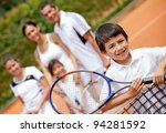 Young male tennis player and his family - stock photo