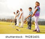 Golf players of all ages practicing to hit the ball at the course - stock photo