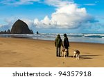 Stock photo winter ocean and beach scene dog walkers looking at dramatic view of haystack rock in cannon beach 94357918