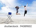 Asian business team jumping on the beach to celebrate their succession - stock photo