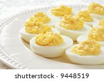 Deviled eggs on a porcelain plate with backlighting reflecting on elegant damask tablecloth.  Close-up with shallow dof. - stock photo