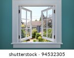 Open window to the back yard with blue wall. - stock photo