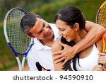 Tennis couple flirting at the court and smiling - stock photo