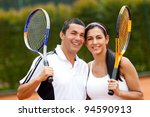 Happy couple of tennis players training outdoors - stock photo