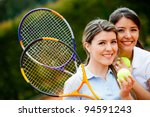 Friendly female tennis players holding rackets and smiling - stock photo