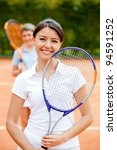 Woman playing doubles at tennis and smiling - stock photo