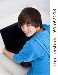 Young teenager with laptop sitting on the floor - stock photo