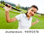Girl playing golf and holding a golf-club at the field - stock photo