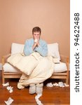 A sick man on the couch blowing his nose - stock photo