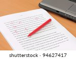 Stock photo proofreading a manuscript beside laptop 94627417