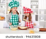 Little chefs making a cake - covering the layers with cream - stock photo