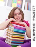 School girl sitting with lots of books smiling - stock photo
