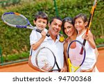 Happy family portrait playing tennis outdoors and smiling - stock photo