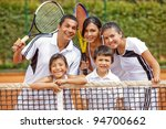 Happy family playing tennis and holding rackets - stock photo