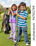 Casual kids at a golf field holding golf-clubs - stock photo