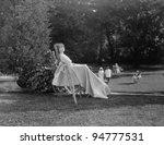 Female patient in wheelchair relaxing in garden - stock photo