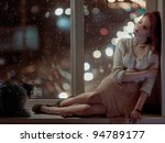 romantic beautiful woman and a cat sitting on a window at winter night - stock photo