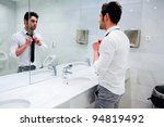 Man getting dressed in a public restroom with mirror - stock photo