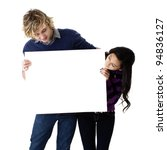 attractive young couple holding a blank sign - stock photo