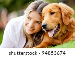 Stock photo portrait of a woman with her beautiful dog lying outdoors 94853674