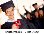 Happy Male Graduate Holding Hi...