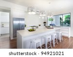 Stylish open plan kitchen overlooking the backyard - stock photo
