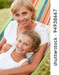 Rest in the garden, happy childhood - girl with mother playing in colorful hammock - stock photo