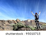 Hiker cheering. Happy hiking woman with arms raised overcoming challenges. From hike on volcano Teide, Tenerife, Canary Islands, Spain. - stock photo