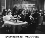 Couple dining in crowded restaurant - stock photo