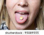 A young girl takes a vitamin c chewable tablet for supplementing her health. - stock photo