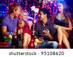 Small photo of Happy friends drinking cocktails and smoking kalian in the nightclub celebrating birthday