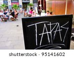 BARCELONA, SPAIN - AUGUST 16: A blackboard with word tapas in a restaurant terrace in Born district on August 16, 2011 in Barcelona, Spain. This district houses a large number of bars and restaurants - stock photo
