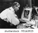 Man looking at portrait of woman - stock photo