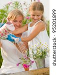 Gardening, planting - mother with daughter watering flowers in the flowerpot - stock photo
