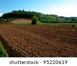 Plowed ground, with brown stones and loose soil - stock photo