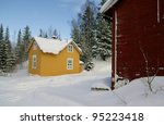 Red shed and yellow house in the snow - stock photo