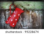 Vintage red jug hanging on rustic wooden wall - stock photo