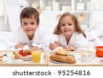 Kids having a healthy and various breakfast in bed - stock photo