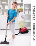 Kids cleaning the room - boy using a vacuum cleaner - stock photo