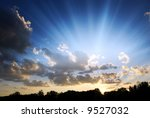 beautiful sunset sky with rays of light from behind the clouds - stock photo