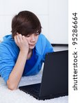 Teenager boy with laptop laying on the floor - computer generation, closeup - stock photo