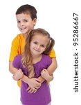Loving siblings - little boy hugging his smaller sister, isolated - stock photo